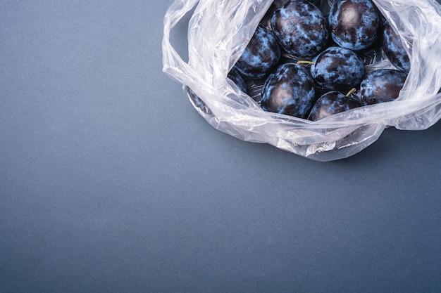 Frutti maturi freschi della prugna nel pacchetto del sacchetto di plastica sul minimo grigio blu