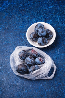 Frutti maturi freschi della prugna nel pacchetto del sacchetto di plastica e nella ciotola di legno sulla tavola astratta blu, vista di angolo