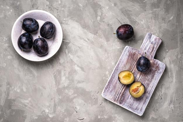 Frutti maturi freschi della prugna interi e affettati in una ciotola e su legno