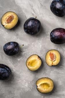 Frutti di prugna maturi freschi interi e affettati sulla tavola di cemento di pietra, vista dall'alto