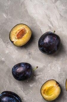 Frutta matura fresca della prugna intera ed affettata sulla pietra Foto Premium