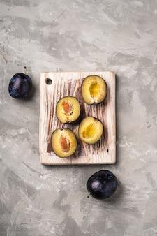 Frutti maturi freschi della prugna interi e affettati sul tagliere di legno, priorità bassa del calcestruzzo di pietra, vista dall'alto