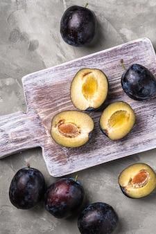 Frutti di prugna maturi freschi interi e affettati sul tagliere di legno, tavolo in cemento di pietra, vista dall'alto