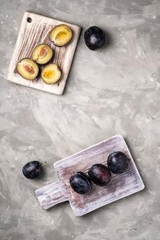 Frutti di prugna maturi freschi interi e affettati su taglieri di legno, sfondo di cemento pietra, spazio di copia vista dall'alto