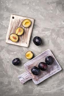 Frutti di prugna freschi maturi interi e affettati su taglieri di legno, tavolo in pietra, vista dall'alto