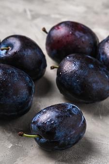 Frutti maturi freschi della prugna con gocce d'acqua sul calcestruzzo di pietra, macro di vista di angolo