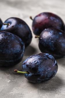 Frutti maturi freschi della prugna con le gocce d'acqua sul fondo del calcestruzzo di pietra, macro di vista di angolo