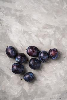Frutti di prugna maturi freschi con gocce d'acqua su sfondo di cemento di pietra, spazio di copia vista dall'alto