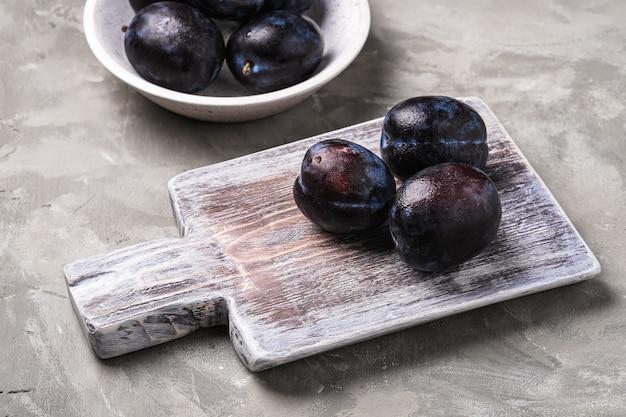 Frutti di prugna freschi maturi con gocce d'acqua in ciotola di legno e tagliere