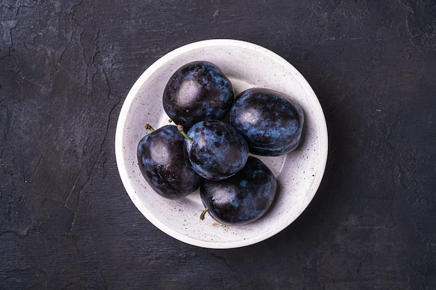 Frutti maturi freschi della prugna con gocce d'acqua nella ciotola di legno sulla pietra scura