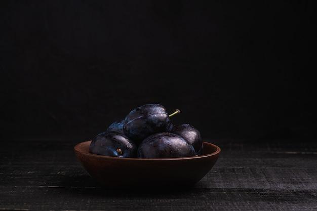 Frutti maturi freschi della prugna con gocce d'acqua nella ciotola di legno su legno scuro