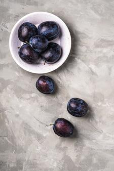Frutti maturi freschi della prugna con gocce d'acqua nella ciotola di legno sul cemento di pietra, vista dall'alto