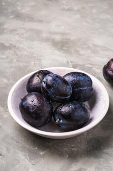 Frutta matura fresca della prugna con le gocce di acqua in ciotola di legno su stone