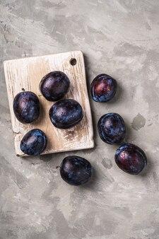 Frutta matura fresca della prugna con le gocce di acqua sul tagliere di legno