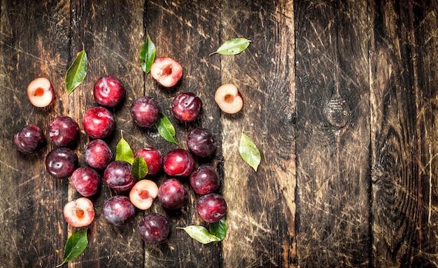 Prugne fresche e mature con foglie. su uno sfondo di legno.