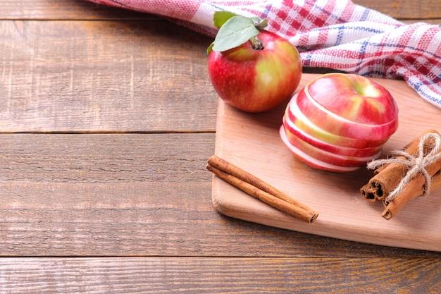 Mele rosse mature fresche su un tagliere con bastoncini di cannella su un tavolo di legno marrone