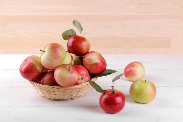 Mele rosse mature fresche con le foglie in un canestro su una tavola di legno bianca e su un fondo di legno naturale