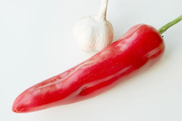 Fresco e maturo rosso georgia fiamma peperone dolce con aglio isolato su sfondo bianco