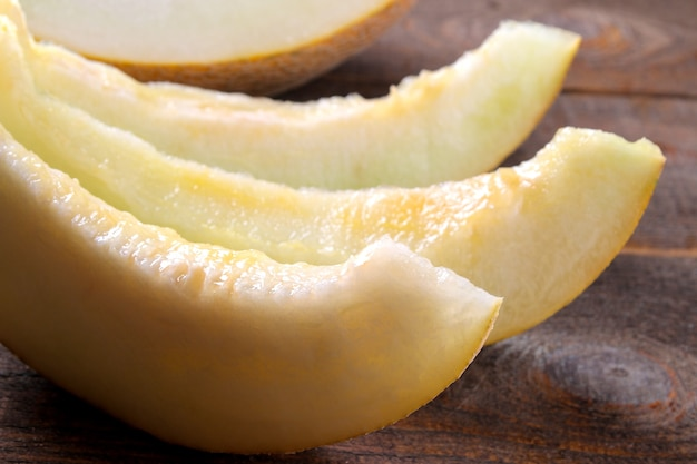 Fette mature fresche di primo piano del melone su una tavola di legno marrone