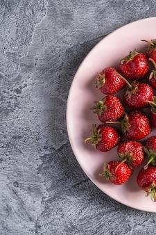 Frutti di fragola matura fresca in zolla rosa, bacche di vitamina estiva sulla superficie di pietra grigia, vista dall'alto