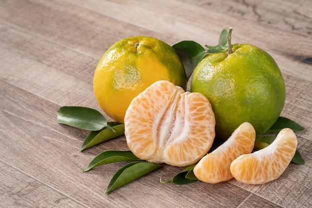 Mandarino mandarino maturo fresco in una scatola con foglie fresche.