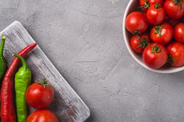 Pomodori maturi freschi in una ciotola vicino al vecchio tagliere di legno con peperoncino, spazio copia cemento pietra