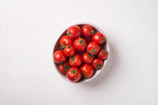 Pomodori maturi freschi in ciotola sulla superficie di cemento bianco