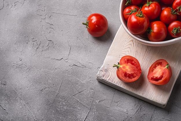 Pomodori maturi freschi interi e affettati in una ciotola e sul vecchio tagliere di legno