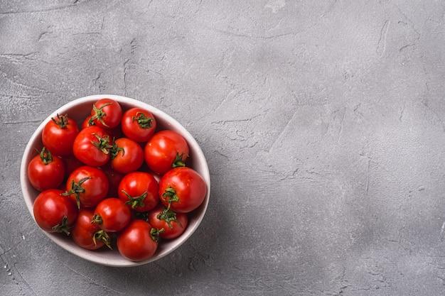 Pomodori maturi freschi con gocce d'acqua nella ciotola