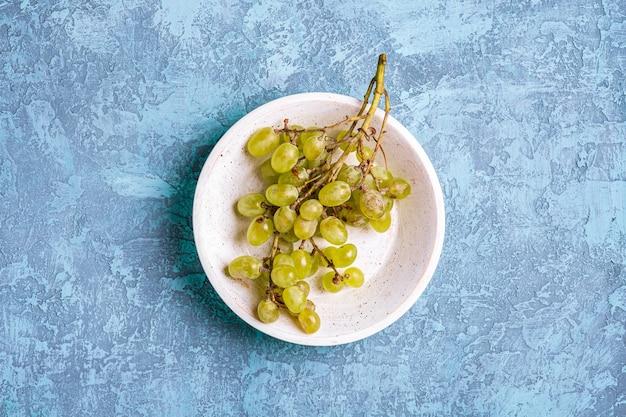 Bacche mature fresche dell'uva bianca in ciotola di legno sull'azzurro