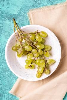 Uva bianca matura fresca in ciotola di legno sulla tovaglia di lino