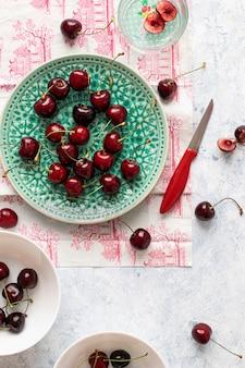Ciliegie rosse fresche strappate su un piatto verde flatlay