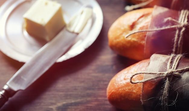 Panini freschi per la colazione. bun con burro per una tazza di caffè al mattino. colazione in hotel con panini alla marmellata e un mazzo di fiori.