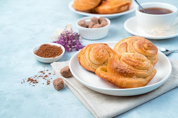 Panini freschi su un piatto, cacao, zucchero e tè su sfondo blu.