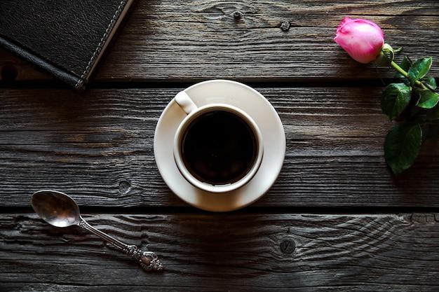 Rose fresche con diario e tazza di caffè sulla tavola di legno, vista dall'alto.