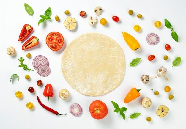 Pasta rotonda fresca con ingredienti per cucinare pizza italiana fatta in casa su sfondo bianco, vista dall'alto piatta