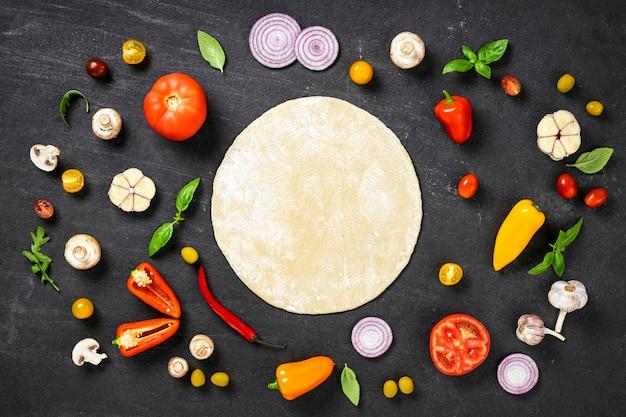 Pasta rotonda fresca con ingredienti per cucinare pizza vegetariana fatta in casa su sfondo nero, vista dall'alto piatta