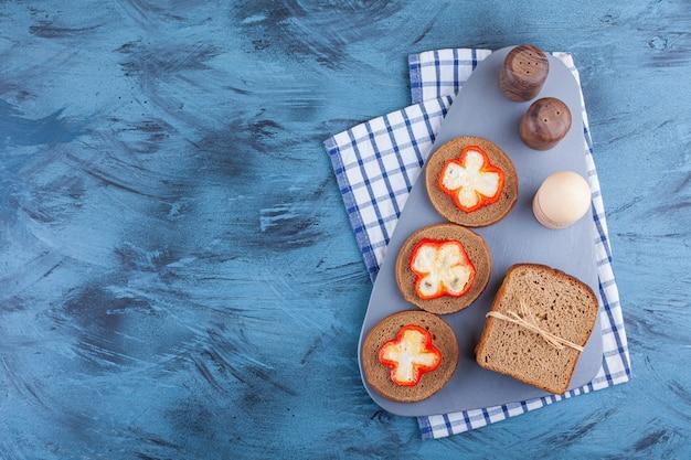 Pane di segale fresco su tavola di legno con uova sode e peperoni.