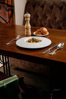 Piatto di insalata fresca con gamberetti, pomodoro e verdure miste sulla superficie in legno si chiuda