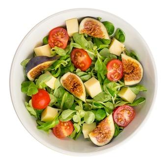 Insalata fresca con fichi, foglie, pomodorini e formaggio su sfondo bianco. concetto di cibo. vista dall'alto.