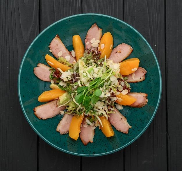 Insalata fresca con carne alla griglia, pesche caramellate e verdure su fondo nero