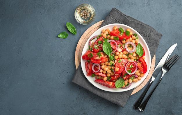 Insalata fresca con pomodori, ceci, cipolle, basilico e olio d'oliva su sfondo grigio-blu scuro. vista dall'alto, spazio per la copia.
