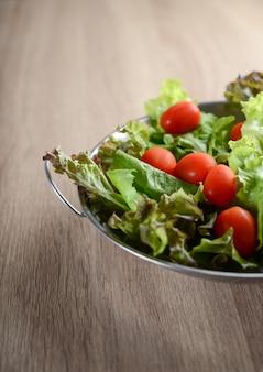 Insalata fresca con verdure e verdure sul tavolo di legno. concetto di cibo sano.