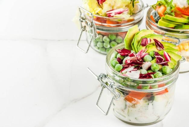 Insalate fresche in barattolo con gli ortaggi freschi e le medicazioni sane, sulla tavola di marmo bianca, copyspace