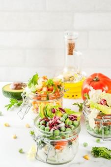 Insalate fresche in barattolo con verdure fresche e condimenti sani, sul tavolo di marmo bianco,