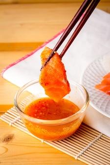 Salmone fresco prelevato da una ciotola di salsa di frutti di mare con una bacchetta di legno