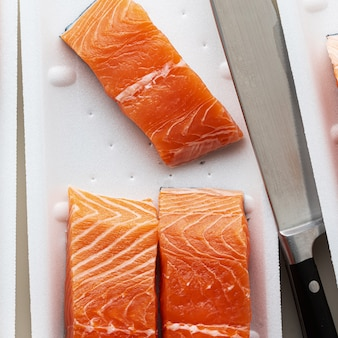 Salmone fresco, tagliato a pezzi e pronto per la cottura., e un grosso coltello da chef.