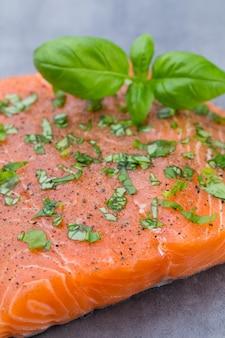 Fille di salmone fresco con spezie sulla superficie grigia.