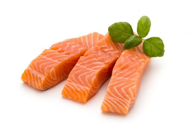 Filetto di salmone fresco con basilico su sfondo bianco.