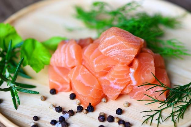 Salmone fresco per cucinare insalata di pesce cibo giapponese, filetto di salmone crudo con salsa wasabi su legno